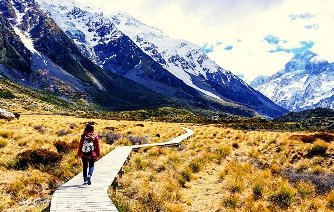 Woman walking on boardwalk across field near mountains
